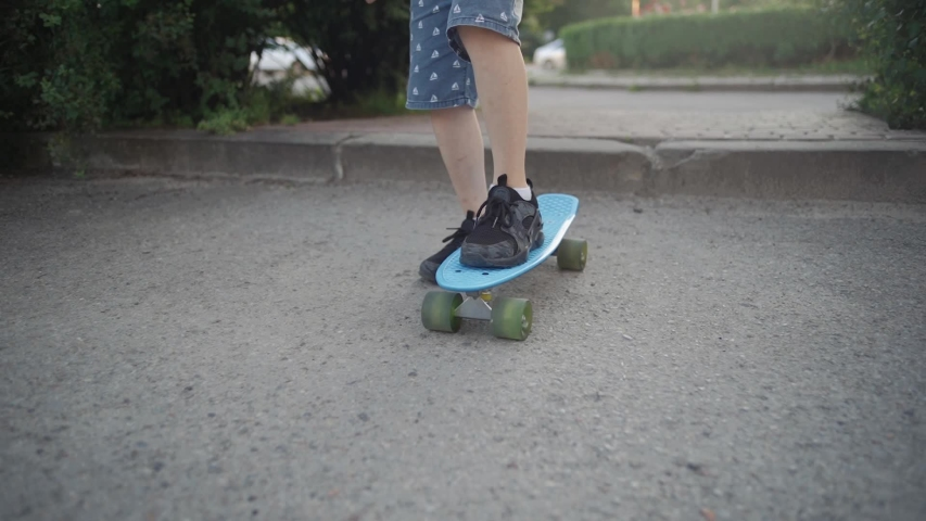A boy learns to skate in a park in the summer. Slow motion | Shutterstock HD Video #1055503007