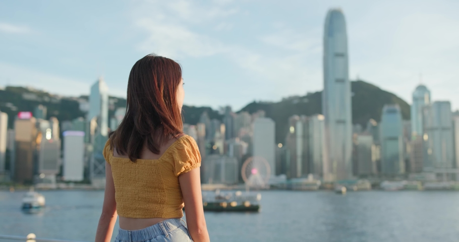 Woman look at the city in Hong Kong at sunset | Shutterstock HD Video #1055512520