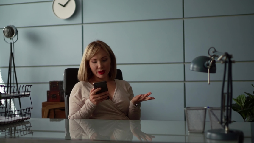 Businesswoman is calling by cellphone sitting in her modern office, working day | Shutterstock HD Video #1055515886