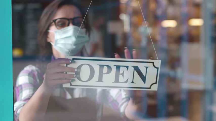 Through glass view of female business owner in safety mask hanging up sign with inscription closed on cafe door. Waitress in protective mask closing restaurant because of pandemic Royalty-Free Stock Footage #1055518799