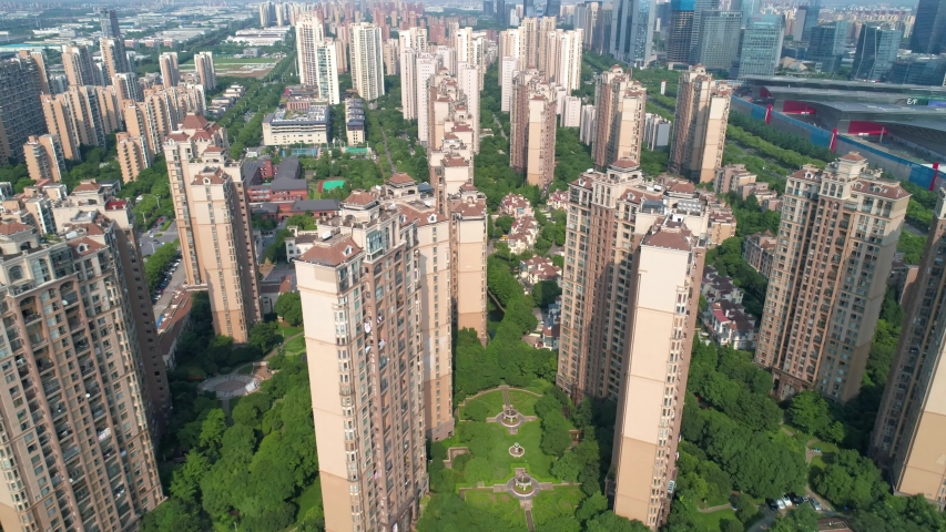 Aerial drone shot over residential apartment buildings on sunny day. Aerial shot over community apartment complex in China. | Shutterstock HD Video #1055519486
