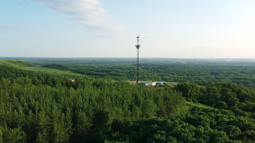 Aerial view of the flight by drone over the trees and next to the antenna. 5g communications tower and television broadcasting. Internet and Communications | Shutterstock HD Video #1055524460
