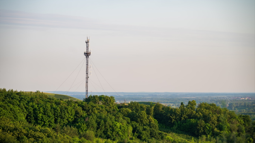 Timelapse. The cell tower stands on a high green hill on the skyline background | Shutterstock HD Video #1055524478
