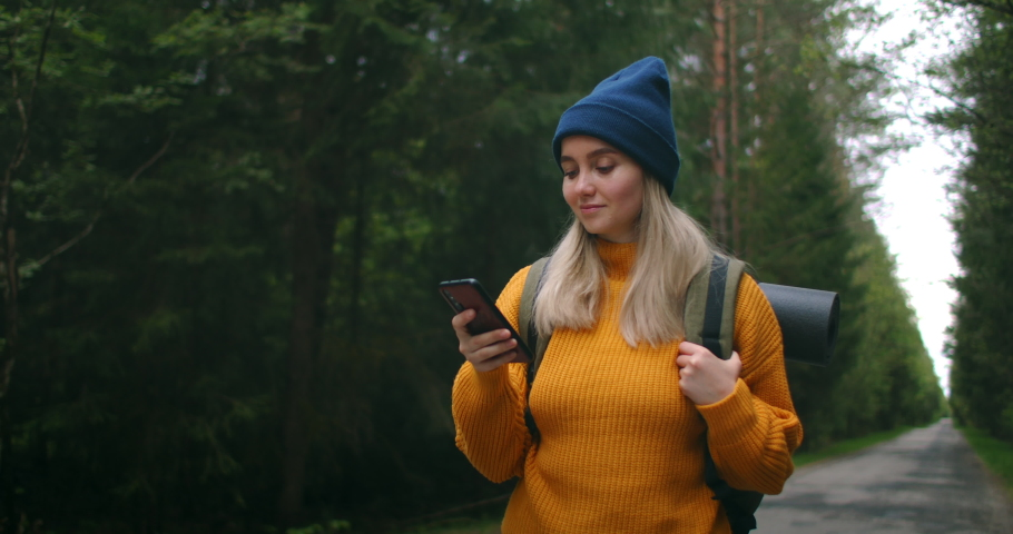 Girl with Backpack Using Smartphone Gps. Woman Hiking In The Forest And Typing Message On Smartphone. Solo female hiker using smart phone. Female hiker takes smart phone pic of mountains and forest. | Shutterstock HD Video #1055524748