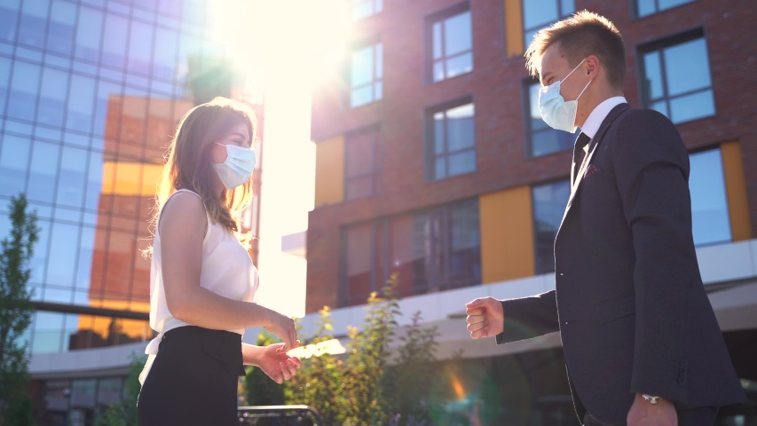 Low angle side view of serious young business partners in formal clothes and medical masks share documents while standing near modern office building in city downtown Royalty-Free Stock Footage #1055527280