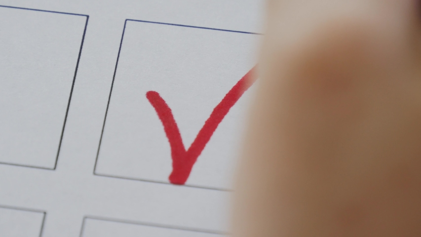 Woman draws a tick on voting blank. Close up hand writing a checkmark. Voting concept | Shutterstock HD Video #1055530523