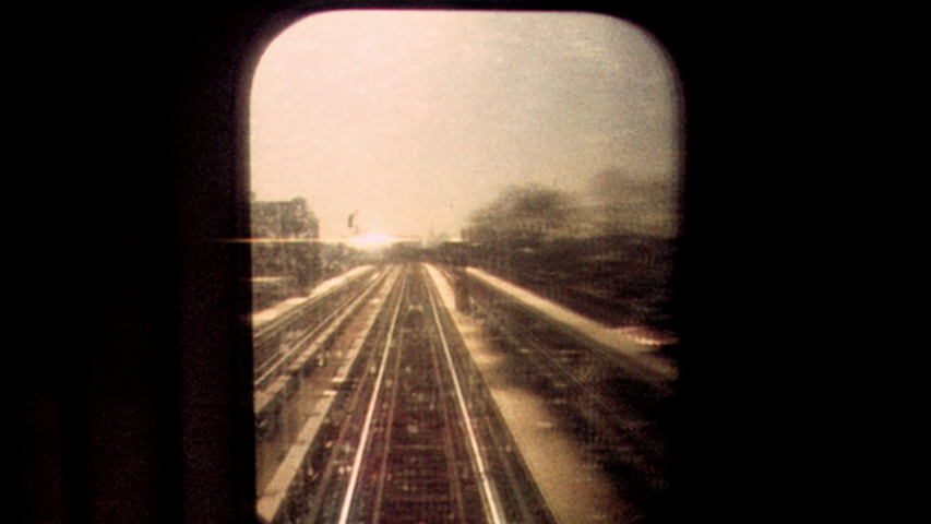 2019: Retro looking footage filmed on Super 8 on the New York City subway looking out through subway window at tracks and passing train with apartments and graffiti in the distance #1055545349