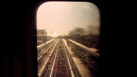 2019: Retro looking footage filmed on Super 8 on the New York City subway looking out through subway window at tracks and passing train with apartments and graffiti in the distance