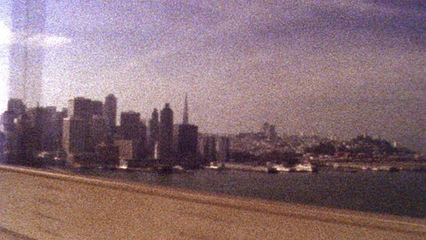 2019: Retro looking footage filmed on Super 8 old looking footage of San Francisco skyline while driving across Golden Gate Bridge Royalty-Free Stock Footage #1055545352