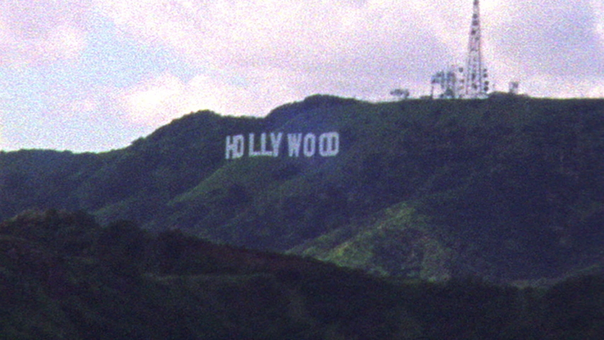 2019: Retro looking footage filmed on Super 8 shaky old looking footage of Los Angeles skyline and Hollywood sign in the distance #1055545355