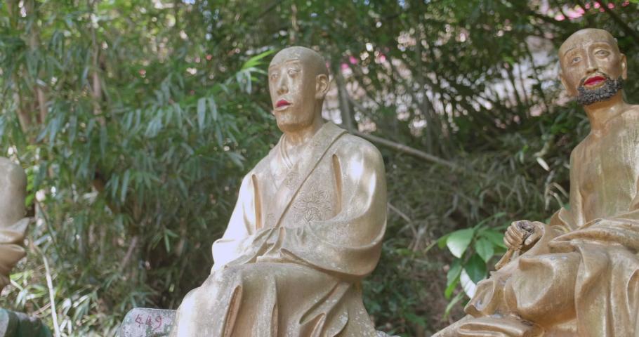 Dolly shot of buddha statues in a row. Ten Thousand Buddhas Monastery, Sha Tin, Hong Kong. Peaceful golden religious figures. High dynamic range footage. | Shutterstock HD Video #1055551412