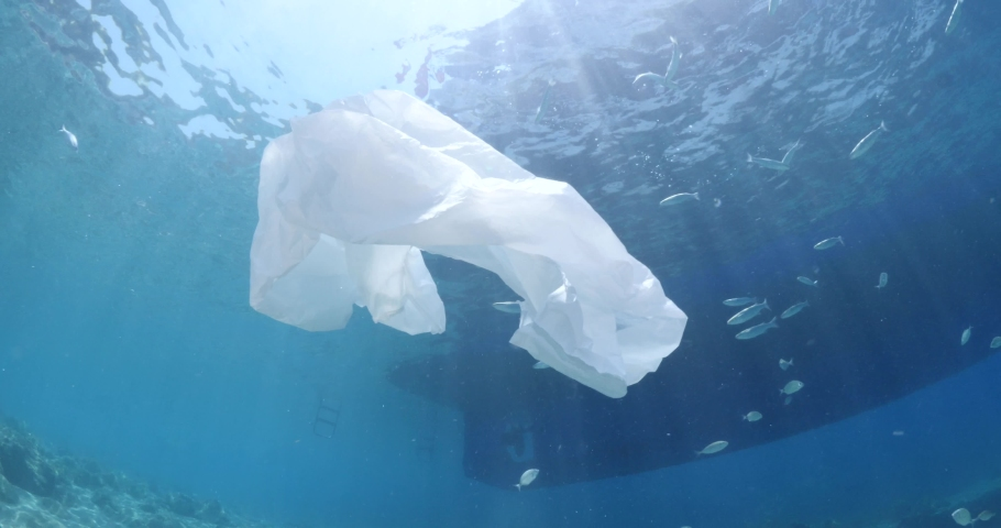 Plastic ocean pollution next to boat on surface of the sea underwater plastic bag | Shutterstock HD Video #1055552438
