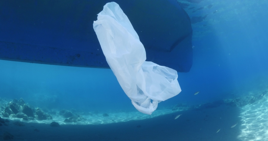 Plastic ocean pollution next to boat on surface of the sea underwater plastic bag | Shutterstock HD Video #1055552441
