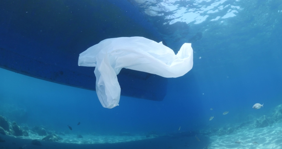 Plastic ocean pollution next to boat on surface of the sea underwater plastic bag | Shutterstock HD Video #1055552444
