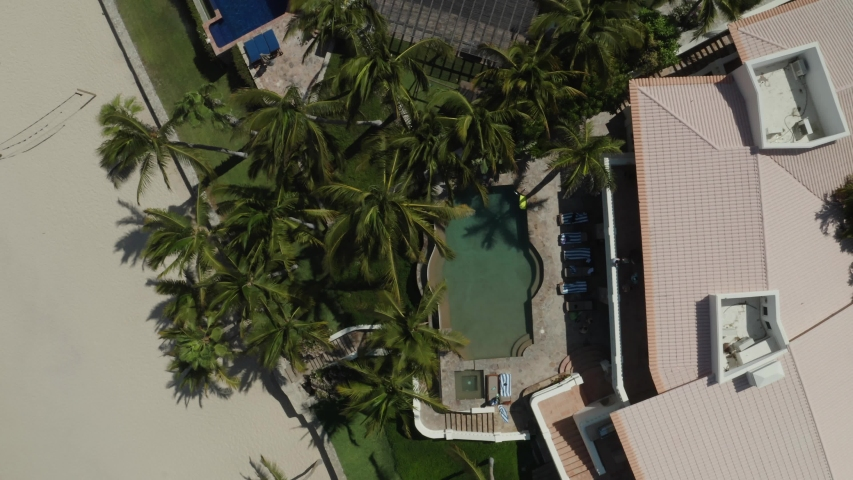 Cabo san Lucas hotel pool. Caucasian tourist jumps into pool. Drone aerial view top down.  | Shutterstock HD Video #1055552801