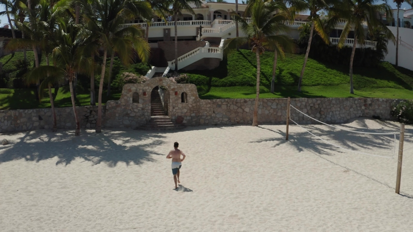 Caucasian male runs up stairs to hotel resort in Cabo San Lucas. Drone aerial view tracks from behind, until going above the hotel.  | Shutterstock HD Video #1055553044
