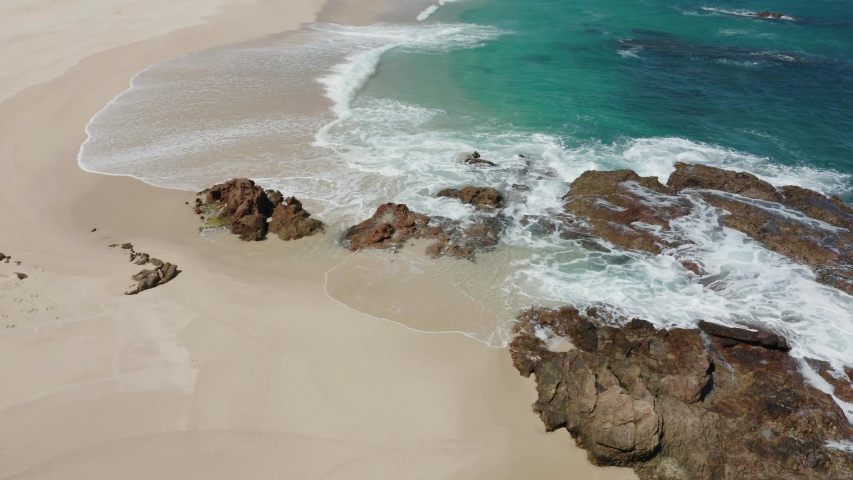 Drone tilts up to reveal beautiful Cabo San Lucas beach resort. Blue water, sunny day.  | Shutterstock HD Video #1055553113