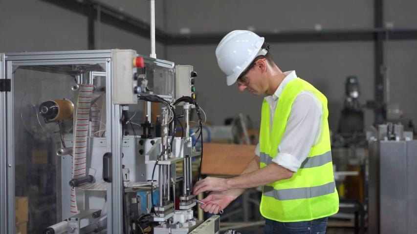 Engineer with helmet is repairing machine in workshop.   Shutterstock HD Video #1055554556