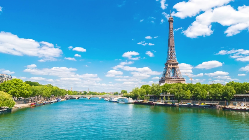 A hyperlapse of the Eiffel Tower along the river Seine with fly boats passing by with motion from left to right.Sunny summer day paris city famous riverside bay tower view bridge timelapse panorama. | Shutterstock HD Video #1055555108