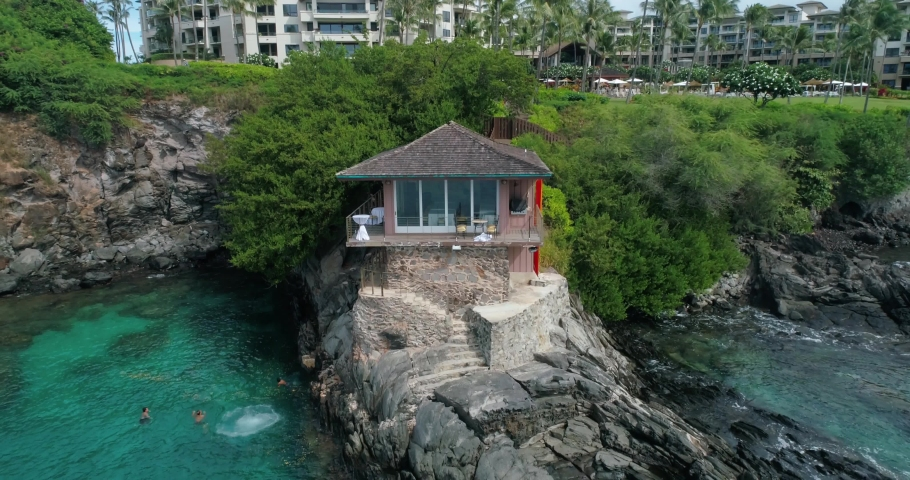 Kapalua cliff house Maui Hawaii. Rocky coastline, house built right on the waters edge. Sunny day. Aerial drone view, camera pulls back.  | Shutterstock HD Video #1055555168