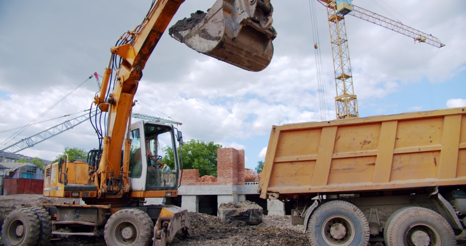 Excavator loads sand into a truck body at a construction site, industry.   Shutterstock HD Video #1055558216
