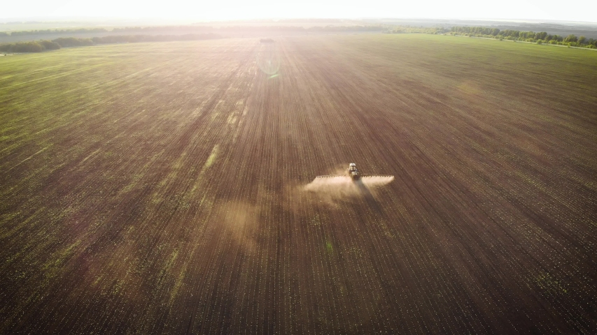 Aerial view of farming tractor spraying on field with sprayer, herbicides and pesticides at sunset. Farm machinery spraying insecticide to the green field, agricultural natural seasonal spring works.   Shutterstock HD Video #1055559065