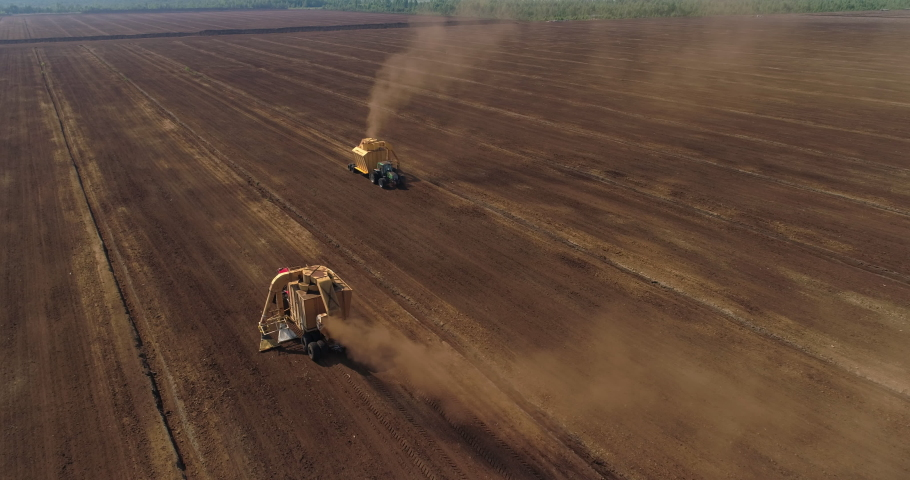 Peat harvesting machinery extracting peat turf in drained bog aerial view   Shutterstock HD Video #1055561669