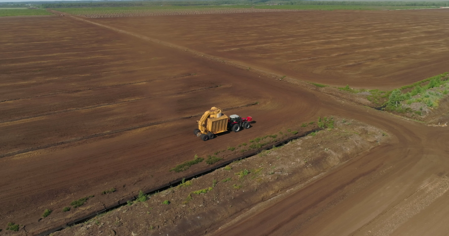 Peat harvesting machinery extracting turf in drained bog aerial view   Shutterstock HD Video #1055561675