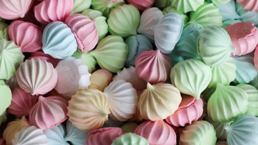 Marshmallows against a background of multicolored meringues closeup. Confectionery zephyr and meringue of a colorful delicate color for the holiday, top view. | Shutterstock HD Video #1055564141