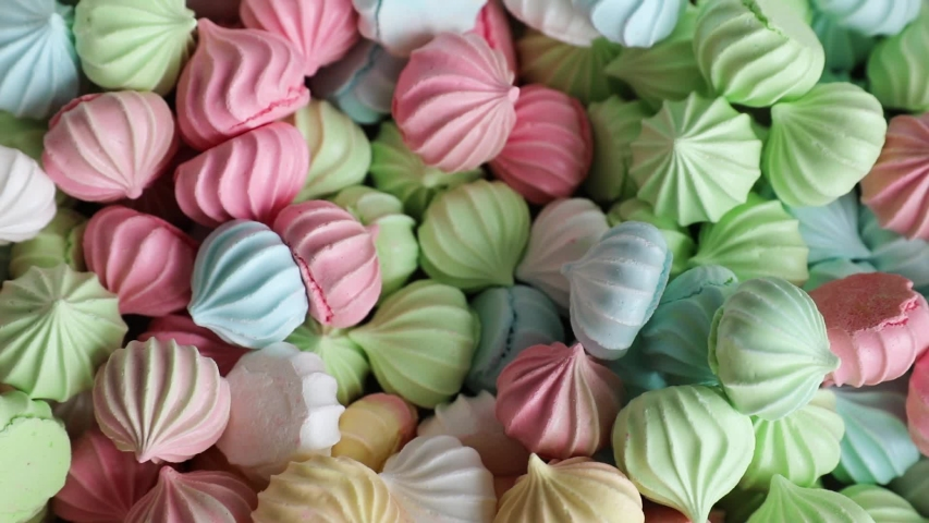 Marshmallows against a background of multicolored meringues closeup. | Shutterstock HD Video #1055564144