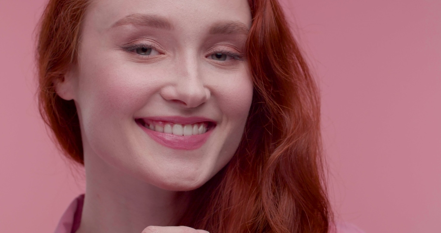 Portrait of Smiling Happy woman looking at Camera and posing in front of Objective. Looking charming and Lovely. Having nice Smile and beautiful Appearance. Attractive model with long Red Hair. | Shutterstock HD Video #1055564615