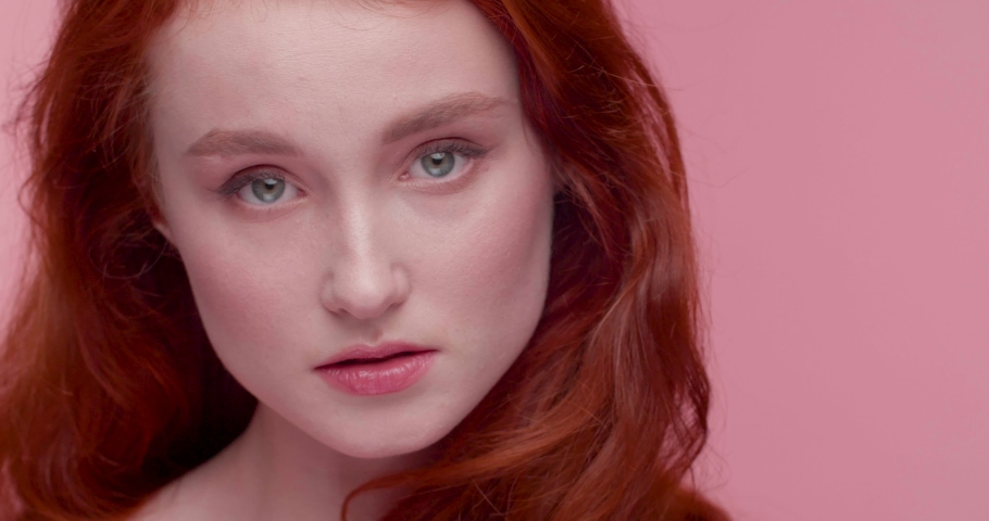 Portrait of Pretty gorgeous Woman with long Beautiful Red Hair posing for Popular Magazine. Makeup Artist applying cosmetics with Brush at same Time. Natural Beauty of Attractive model. | Shutterstock HD Video #1055564621