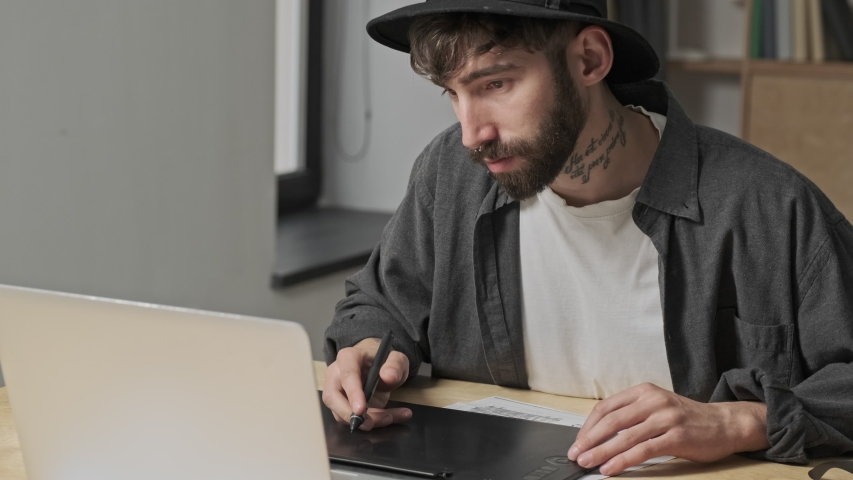 A handsome artist man is working using his digital tablet in the office | Shutterstock HD Video #1055569163