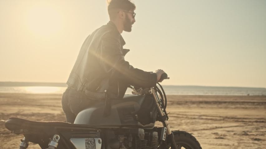 A brutal happy young man rolls a motorcycle while walking on the beach | Shutterstock HD Video #1055569316