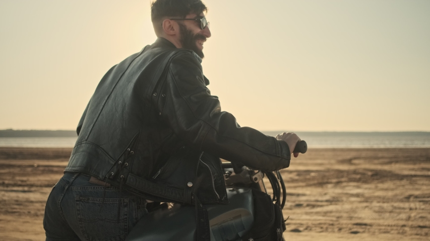 A brutal confident young man rolls a motorcycle while walking on the beach | Shutterstock HD Video #1055569319