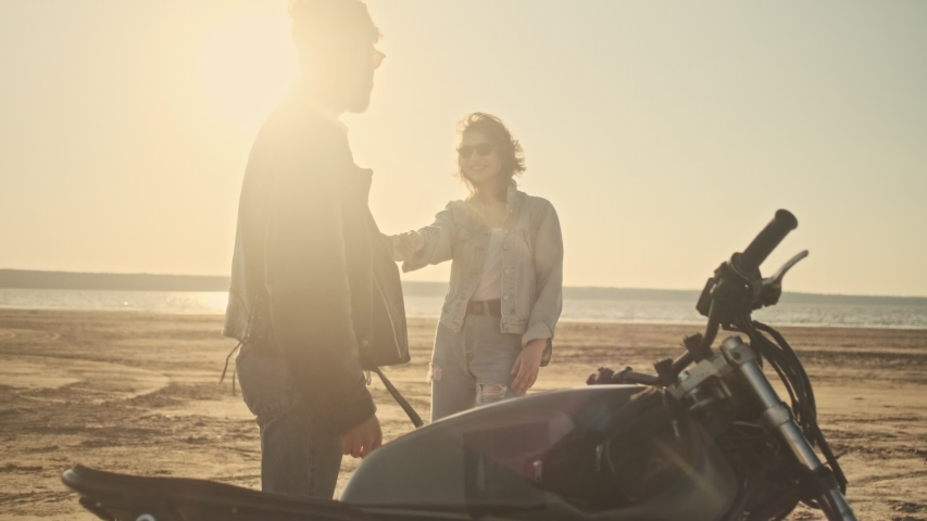 An attractive young couple man and woman in love are walking on the beach during riding a motorbike | Shutterstock HD Video #1055569322