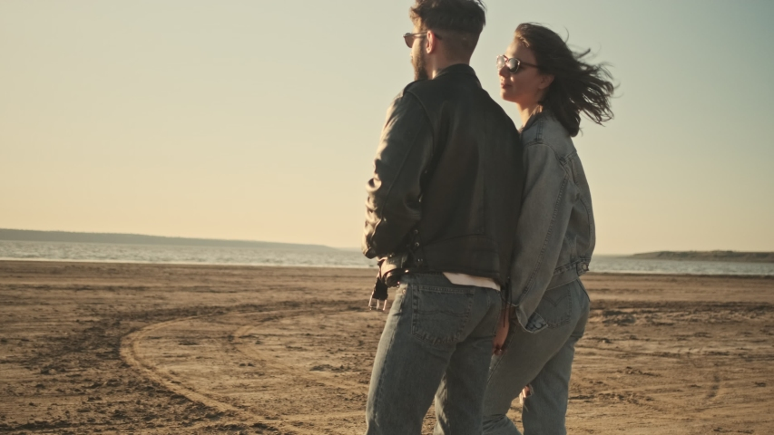 A charming young couple man and woman are walking on the beach | Shutterstock HD Video #1055569325