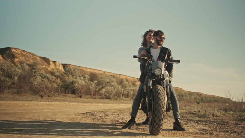 A happy young couple man and woman are riding on a motorbike together on the beach | Shutterstock HD Video #1055569328