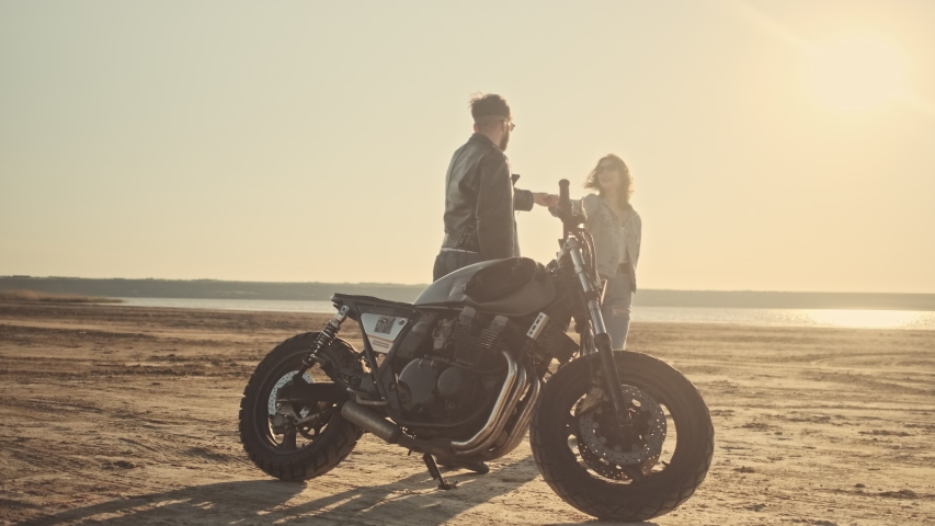 A young couple man and woman in love are walking on the beach during riding a motorbike | Shutterstock HD Video #1055569337