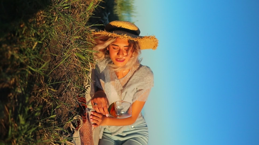 Young curly blonde with a glass in hand in a straw hat with daisies in a basket on a sky background camera rotation | Shutterstock HD Video #1055569631