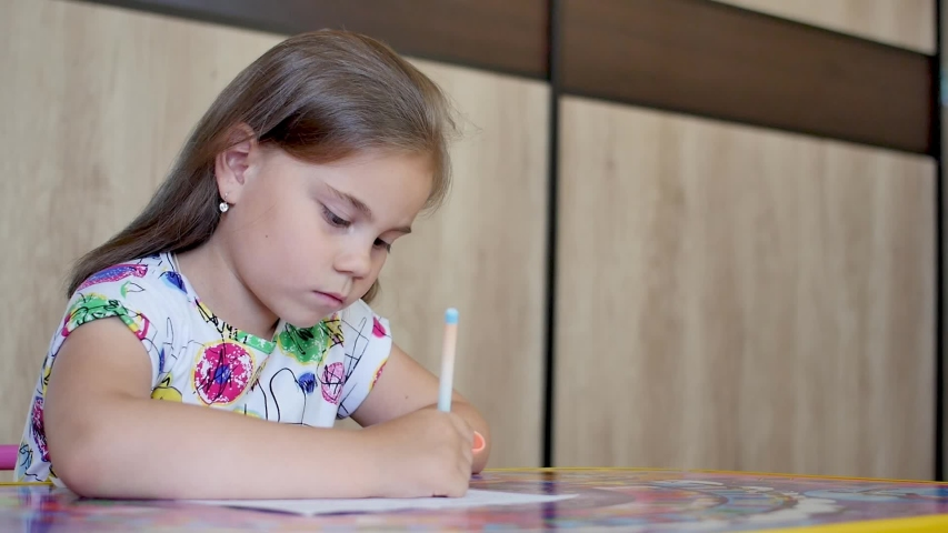 Happy little girl or cute primary child school child painting or writening on paper. Children elementary education concept. | Shutterstock HD Video #1055569709