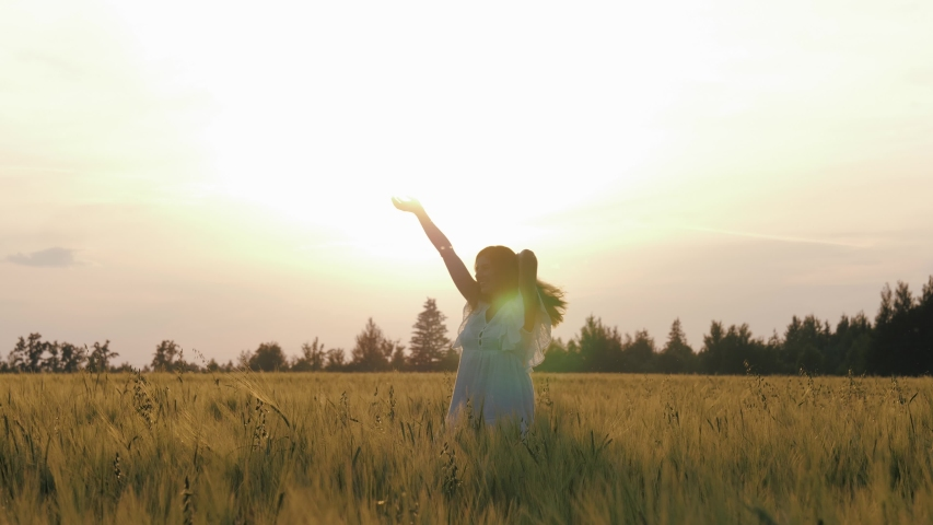 Happy caucasian woman in white dress turning around on golden wheat agricultural field in light of sunset. Raises her hands up and arms to sides. Enjoying evening and freedom lifestyle, slow motion | Shutterstock HD Video #1055570297