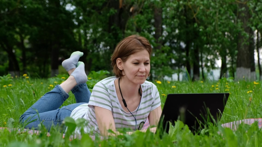 Young woman sitting in a park and working on computer laptop outside | Shutterstock HD Video #1055570828