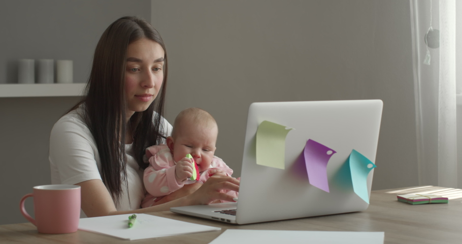 The mother is working on a laptop. The baby is playing with a toy. Work at home. 4K | Shutterstock HD Video #1055571362