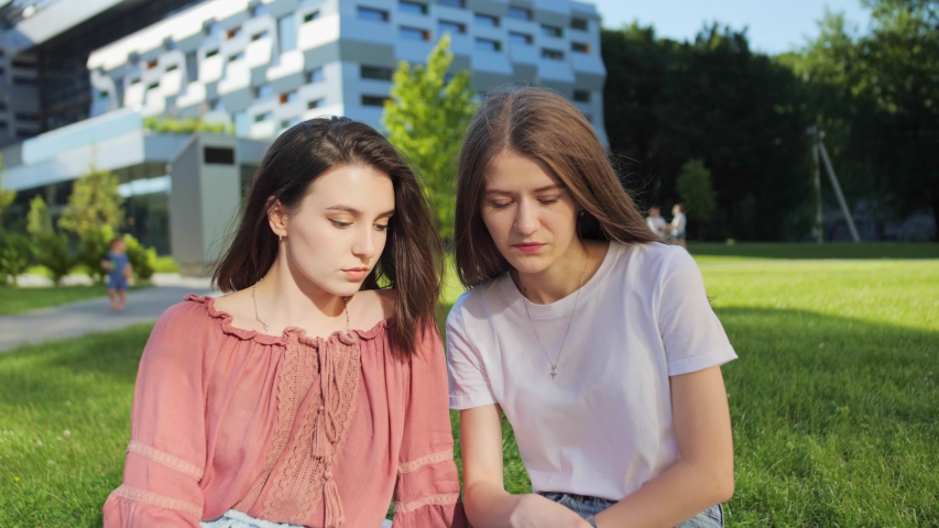 Two pretty female students are studying a lecture remotely on a laptop outdoors on the background of modern building | Shutterstock HD Video #1055572085