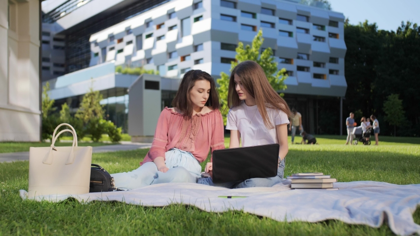 Two pretty female students are studying a lecture remotely on a laptop outdoors on the background of the university | Shutterstock HD Video #1055572121