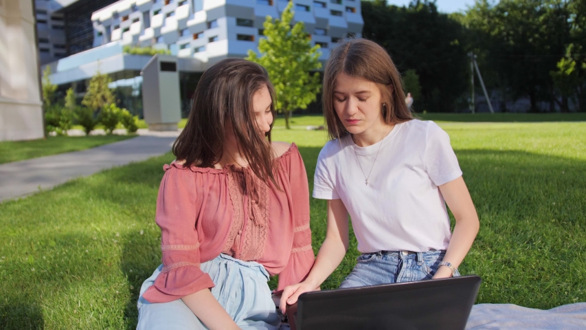 Two pretty female students are studying a lecture remotely on a laptop outdoors on the background of modern building | Shutterstock HD Video #1055572148