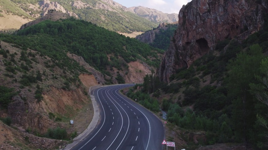 Empty endless serpentine autobahn road / two sided highway in rocky mountains landscape at summer sunset / Aerial drone top view   Shutterstock HD Video #1055578586