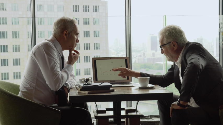 Two senior businessman in meeting pointing graph in laptop analyzing  data information . old man ceo discussing with client in cafe. serious mature manager talking by window over cityscape luxury
