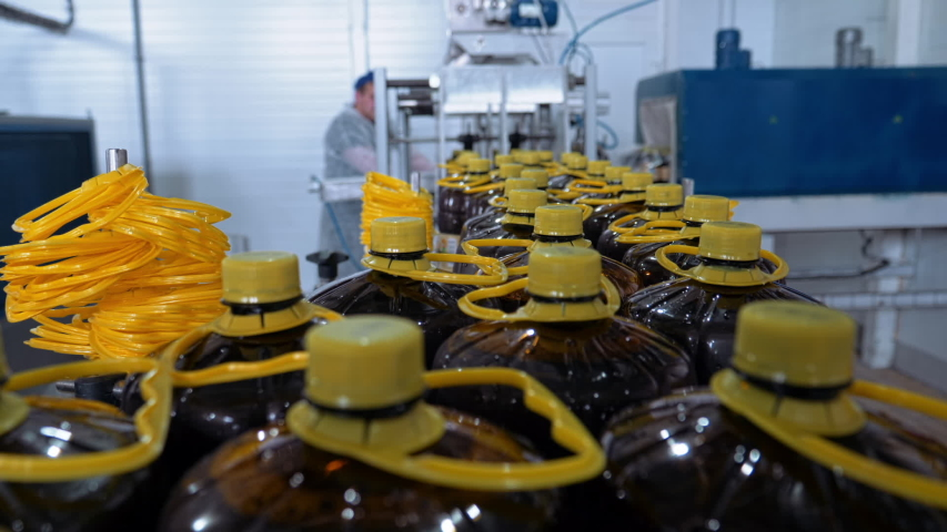 Dark plastic bottles with beer, soft drink, beverage on automated industrial line, close up, yellow caps, slow motion | Shutterstock HD Video #1055581673